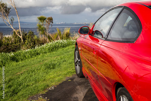 Papel de parede Beautiful, shiny red sports car sitting at the top of a hill looking over Auckland city with native bush