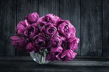 Bouquet Of Purple Tulips In A Vase On A Wooden Wall Background