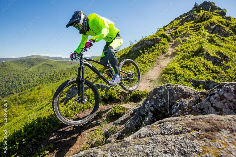 Fototapeta Professional athlete is riding enduro bicycle on a beautiful rocky trail.