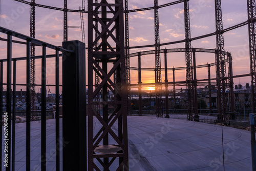 Fototapeta Silhouette of an empty gas storage cylinders against the dusk sunset sky in  London
