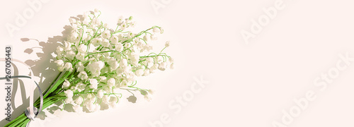 A bouquet of lilies of the valley on a pink background. Isolated, selective focus, copy space. Banner