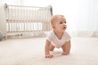 Leinwandbild Motiv Cute little baby crawling on carpet indoors