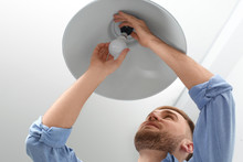 Man Changing Light Bulb In Lamp Indoors