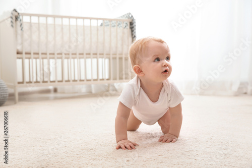 Cute little baby crawling on carpet indoors