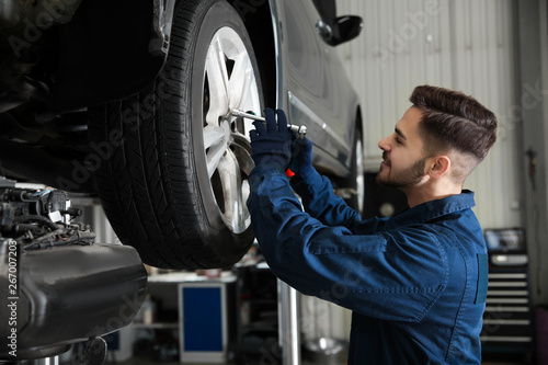 Technician working with car in automobile repair shop