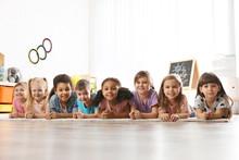 Group Of Cute Little Children Lying On Floor Indoors. Kindergarten Playtime Activities