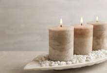 White Plate With Three Burning Candles And Rocks On Table. Space For Text