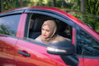 Young Muslim woman looking through car window with face expression, female drivers concept.