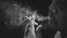 Focus At Hand Of Asian Man Is Smoking Cigarette In Dark Tone With Black And White Style