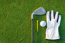 The Golf Sport Equipment  White Glove ,golf Ball, Golf Club And  Yellow Tee Golf With Green Grass Background.