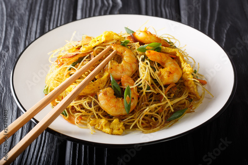 Hot chow Mei Fun rice noodles fried with sausage, shrimps and vegetables close-up on a plate. horizontal