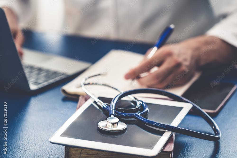 Fototapeta Doctor working in hospital office. Medical healthcare concept.