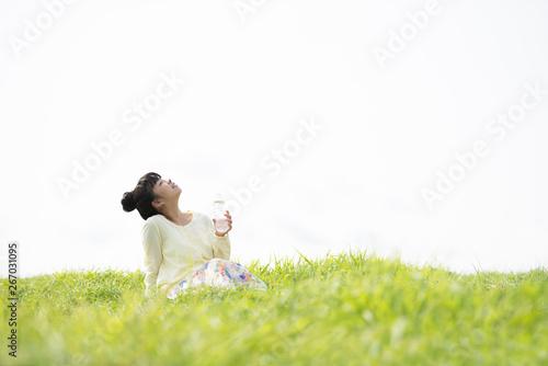Fotografie, Obraz  草原で水分補給をする女性