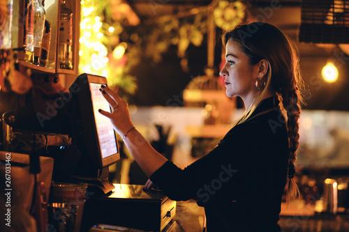 Concepto pequeño negocio o emprendimiento personal: una joven camarera en la máquina registradora de un bar o restaurante