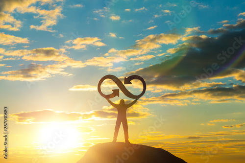 A silhouette of a man holds an infinity symbol on top of a mountain with a sunset background Canvas Print