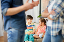 Family Problem, Conflict And People Concept - Sad Children Watching Their Parents Quarreling At Home