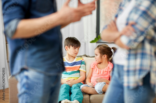 Fotografiet  family problem, conflict and people concept - sad children watching their parent