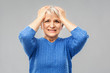 stress, emotions and old people concept - portrait of stressed senior woman in blue sweater holding to her head over grey background