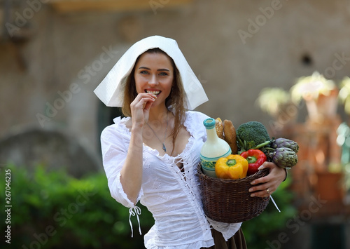 Young pretty peasant woman with a basket of vegetables Wallpaper Mural