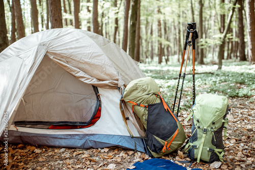 Photo Campsite with tent, backpacks and trekking sticks in the forest