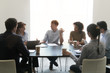 Diverse employees negotiate brainstorming in conference room