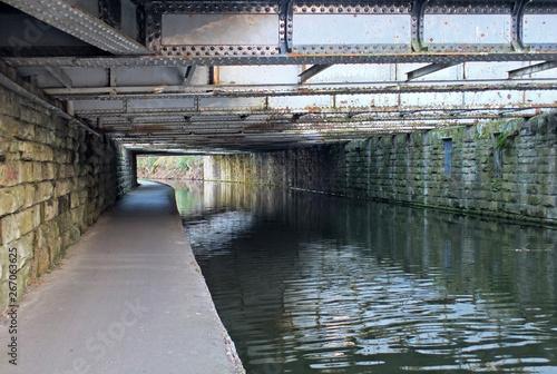 Fotografía view under an old low steel girder bridge crossing the leeds to liverpool canal