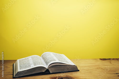 Bible on a brown wooden table. Beutiful yellow wall background. Canvas Print