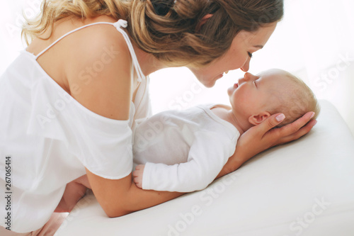 Fototapeta Young mother holding her newborn child. Mom nursing baby. Woman and new born boy relax. Nursery interior. Mother breast feeding baby. Family at home. Portrait of happy mother and baby  obraz