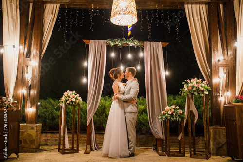 Fotografie, Obraz  beautiful wedding couple the bride and groom stand on the night wedding ceremony