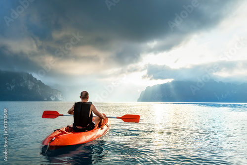 Valokuvatapetti Man floating on kayak under sunrise sky on Cheow Lan Lake, Khao Sok national par