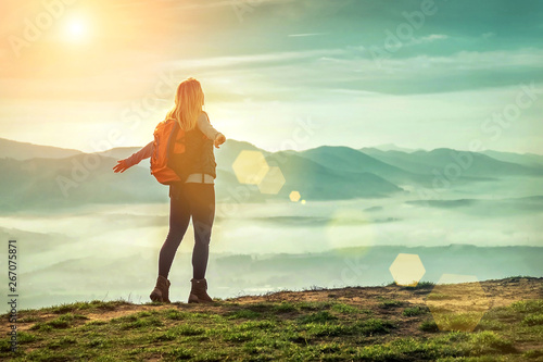 Printed kitchen splashbacks Beige Happy woman tourist stay on the green grass on the peak of mount