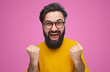 Happy bearded man wearing glasses standing with fists up on pink background. Epic win concept