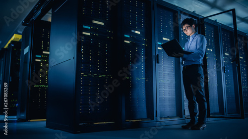 Photographie In Data Center: Male IT Technician Running Maintenance Programme on a Laptop, Controls Operational Server Rack Optimal Functioning
