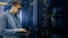 In Data Center IT Engineer Stands Before Working Server Rack Doing Routine Maintenance Check And Diagnostics Using Laptop. Visible Computer Hardware Equipment, Broadband Fiber Optic Cables LED Lights.