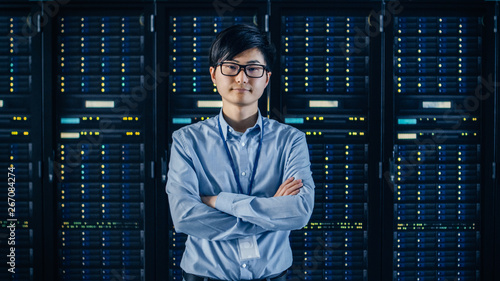 Canvas Print In the Modern Data Center: Portrait of IT Engineer Standing with Server Racks Behind Him, Crossing Arms
