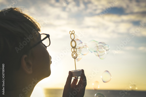 Young blonde boy blows a long string of bubbles in a field; Cute child in front Canvas Print