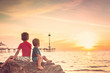 canvas print picture - Two boys sitting on the rock at the beach at sunset