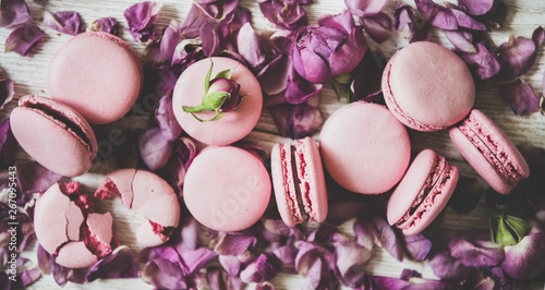 Foto auf AluDibond Macarons Flat-lay of sweet pink macaron cookies and rose buds and petals over wooden background, top view, close-up. Food texture, background and wallpaper