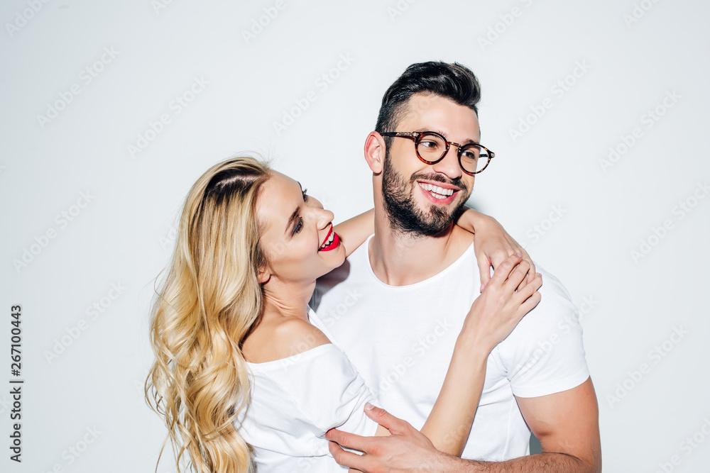 Leinwandbild Motiv - LIGHTFIELD STUDIOS : happy blonde girl looking at handsome man in glasses smiling on white