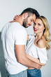 Leinwandbild Motiv handsome man with closed eyes hugging cheerful blonde girl on white