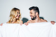 Leinwandbild Motiv happy blonde woman and handsome man looking at each other while holding blanket on white