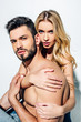 Leinwandbild Motiv blonde woman touching handsome shirtless boyfriend and looking at camera on white