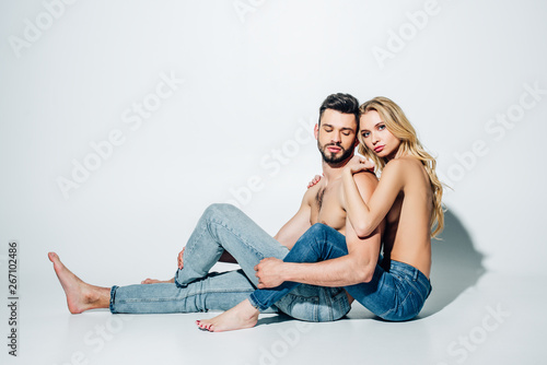 Poster de jardin Individuel attractive blonde girl hugging shirtless boyfriend while sitting on white