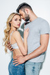 Leinwandbild Motiv attractive blonde woman looking at camera while standing with handsome man on white