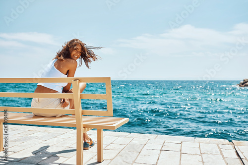 Beautiful girl sitting on bench near the beach  .