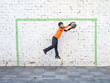 goalkeeper catches the ball in front of a goal painted on the wall