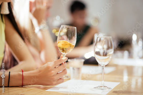 Fotomural  Hand is pouring a bottle of light dry wine into glasses for tasting during the celebration