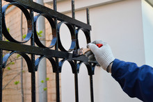 Worker Paints A Fence In Black