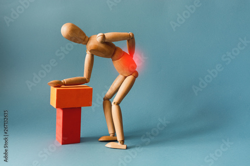 Concept of back pain. A wooden figure depicts a pain in the back. Wallpaper Mural