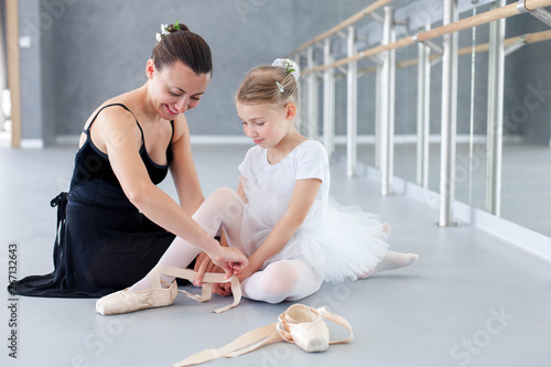 Obraz Adult and little ballerinas are trying on pointe shoes in ballet class. Cute kid girl and young woman are smiling and sitting on floor under barre in dance school. Ballet teacher helps child. - fototapety do salonu
